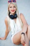 Κορίτσι με τα ακουστικά σε ένα μπλε υπόβαθρο στοκ φωτογραφίες με δικαίωμα ελεύθερης χρήσης