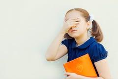 Κορίτσι με τα βιβλία ενάντια στον τοίχο στοκ φωτογραφία με δικαίωμα ελεύθερης χρήσης