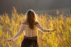 Κορίτσι με τα βουνά δερματοστιξιών στον ώμο που στέκεται και που στον τομέα των καλάμων/ξανθό κορίτσι που περπατά μέσω του τομέα  Στοκ εικόνα με δικαίωμα ελεύθερης χρήσης