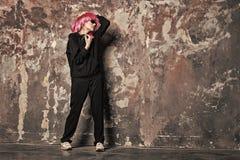 Κορίτσι με τα γυαλιά ηλίου, ακουστικά στον αφηρημένο τοίχο, εκλεκτής ποιότητας φίλτρο στοκ φωτογραφία