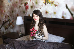 Κορίτσι με τα κόκκινα λουλούδια στο κρεβάτι Στοκ Εικόνες