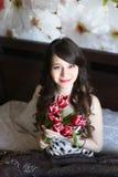 Κορίτσι με τα κόκκινα λουλούδια στο κρεβάτι Στοκ φωτογραφία με δικαίωμα ελεύθερης χρήσης