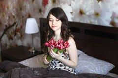 Κορίτσι με τα κόκκινα λουλούδια στο κρεβάτι Στοκ Εικόνα