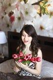 Κορίτσι με τα κόκκινα λουλούδια στο κρεβάτι Στοκ εικόνα με δικαίωμα ελεύθερης χρήσης