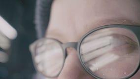 Κορίτσι με τα μάτια γυαλιών που εξετάζει τη κάμερα, ακραία κινηματογράφηση σε πρώτο πλάνο με την αντανάκλαση απόθεμα βίντεο