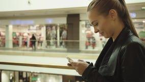 Κορίτσι με τα μακριά ξανθά μαλλιά με το κινητό τηλέφωνο απόθεμα βίντεο