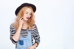 Κορίτσι με τα μακριά ξανθά μαλλιά στα τζιν στο λευκό Στοκ Φωτογραφία