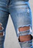 Κορίτσι με τα μακριά πόδια που φορούν το μοντέρνο σχισμένο παντελόνι τζιν Στοκ Εικόνα