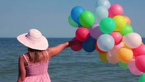 Κορίτσι με τα μπαλόνια στην παραλία απόθεμα βίντεο