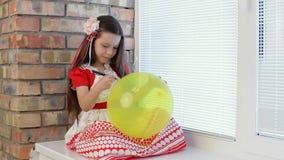 Κορίτσι με τα μπαλόνια στο παράθυρο απόθεμα βίντεο