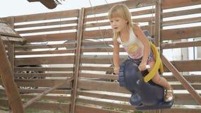 Κορίτσι με τα ξανθά μαλλιά που ταλαντεύονται σε μια ταλάντευση αλόγων σε αργή κίνηση 4k φιλμ μικρού μήκους
