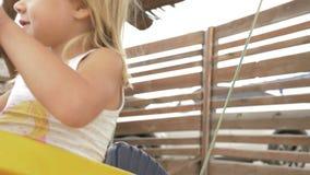 Κορίτσι με τα ξανθά μαλλιά που ταλαντεύονται σε μια ταλάντευση αλόγων 4k απόθεμα βίντεο