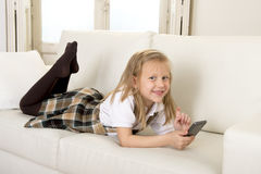 Κορίτσι με τα ξανθά μαλλιά που βρίσκονται στον εγχώριο καναπέ που χρησιμοποιεί Διαδίκτυο app στο κινητό τηλέφωνο Στοκ Εικόνες
