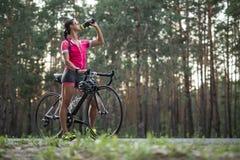 Κορίτσι με τα ποτά ποδηλάτων από τη φιάλη στοκ φωτογραφίες με δικαίωμα ελεύθερης χρήσης