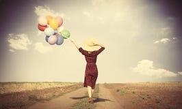Κορίτσι με τα πολύχρωμες μπαλόνια και την τσάντα Στοκ Εικόνα