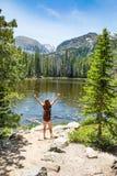 Κορίτσι με τα χέρια που στέκονται επάνω στο βράχο στο ταξίδι πεζοπορίας στα βουνά στοκ φωτογραφία