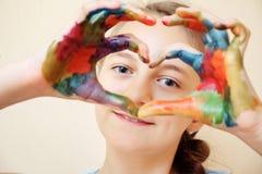 Κορίτσι με τα χρωματισμένα χέρια που κάνει τη μορφή καρδιών στοκ εικόνες με δικαίωμα ελεύθερης χρήσης