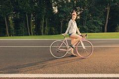 Κορίτσι με τα dreadlocks στο ποδήλατο στον πράσινο δρόμο πόλεων Στοκ Εικόνα