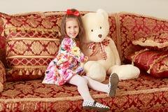 Κορίτσι με την αρκούδα στον καναπέ Στοκ Φωτογραφία