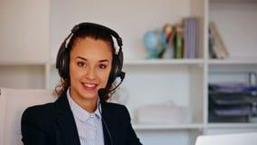 Κορίτσι με την κάσκα και lap-top που απαντά στην κλήση στην αρχή απόθεμα βίντεο