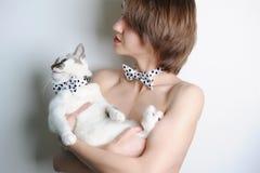 Κορίτσι με την μπλε-eyed γάτα Στο ίδιο σημείο Πόλκα δεσμών τόξων Χωρίς ιματισμό Μοντέρνο διπλός-βλέμμα Άσπρη ανασκόπηση Στοκ φωτογραφία με δικαίωμα ελεύθερης χρήσης