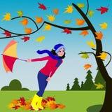 Κορίτσι με την ομπρέλα στο θυελλώδη καιρό κοντά στο δέντρο φθινοπώρου στο δασικό υπόβαθρο απεικόνιση αποθεμάτων
