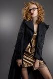κορίτσι με την πανέμορφη τρίχα και όμορφα μάτια σε ένα σαγηνευτικό κοντό χρυσό φόρεμα και γκρίζο παλτό στο γοτθικό ύφος Στοκ φωτογραφία με δικαίωμα ελεύθερης χρήσης
