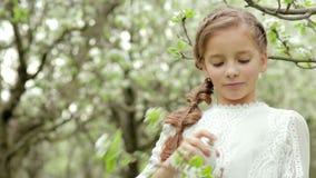 Κορίτσι με την πλεξούδα που φορά αρώματα ενός στα άσπρα φορεμάτων ρουθουνίσματος στο μπουκάλι και τον ανθίζοντας κλάδο στον κήπο  απόθεμα βίντεο