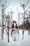 Κορίτσι με την τσάντα στο χιόνι μεταξύ Hogweed Στοκ Εικόνες