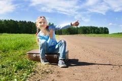 Κορίτσι με τη βαλίτσα που στέκεται για το δρόμο στοκ εικόνα