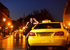 Κορίτσι με τη γοητεία Makeup κορίτσι στη μαύρη στάση φορεμάτων στο κίτρινο αυτοκίνητο ταξί στοκ φωτογραφίες
