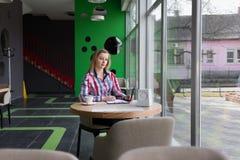 Κορίτσι με τη διαθέσιμη συνεδρίαση χεριών μανδρών σε έναν καφέ Στοκ Εικόνες