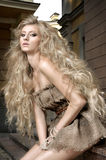 Κορίτσι με τη μακριά ξανθή σγουρή τρίχα στο κοντό φόρεμα Στοκ Φωτογραφίες