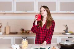 Κορίτσι με τη μακριά ρέοντας τρίχα σε ένα κόκκινο πουκάμισο των ατόμων φλυτζάνι κουζινών τα χέρια του Στοκ εικόνα με δικαίωμα ελεύθερης χρήσης