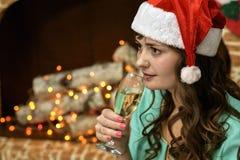 Κορίτσι με τη σαμπάνια στο σπίτι κοντά στην εστία και το χριστουγεννιάτικο δέντρο Στοκ εικόνες με δικαίωμα ελεύθερης χρήσης
