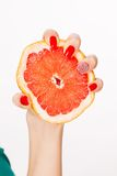 Το χέρι με τα κόκκινα καρφιά συμπιέζει το γκρέιπφρουτ στοκ φωτογραφίες με δικαίωμα ελεύθερης χρήσης