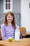 Κορίτσι με τη Apple και συνεδρίαση γάλακτος στον πάγκο στρατοπέδευσης Στοκ εικόνες με δικαίωμα ελεύθερης χρήσης