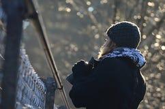 Κορίτσι με τις διόπτρες που κοιτάζει πέρα από το φράκτη καλωδίων Στοκ Εικόνα