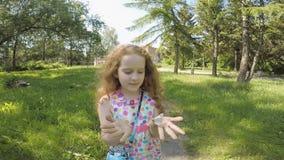 Κορίτσι με τις πεταλούδες στα χέρια ένα θερινό πάρκο φιλμ μικρού μήκους