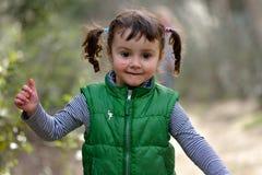 Κορίτσι με τις πλεξίδες που τρέχουν στο parkland, με τη μάνδρα στο πρόσωπο Στοκ Φωτογραφίες