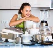 Κορίτσι με τις συσκευές κουζινών στο σπίτι Στοκ Φωτογραφίες