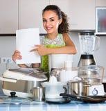 Κορίτσι με τις συσκευές κουζινών στο σπίτι Στοκ Φωτογραφία