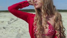 Κορίτσι με τον τέλειο αριθμό στο μαγιό στην παραλία απόθεμα βίντεο