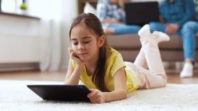 Κορίτσι με τον υπολογιστή ταμπλετών που βρίσκεται στο πάτωμα στο σπίτι απόθεμα βίντεο
