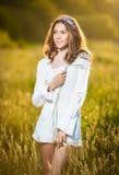 Κορίτσι με το άσπρο πουκάμισο στον τομέα στο ηλιοβασίλεμα Στοκ Φωτογραφία