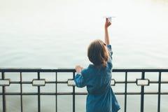 Κορίτσι με το αεροπλάνο εγγράφου παιχνιδιών που κοιτάζει στη λίμνη Στοκ φωτογραφία με δικαίωμα ελεύθερης χρήσης