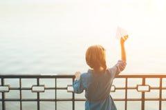 Κορίτσι με το αεροπλάνο εγγράφου παιχνιδιών που κοιτάζει στη λίμνη Στοκ εικόνα με δικαίωμα ελεύθερης χρήσης