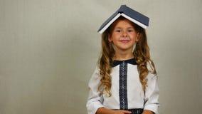 Κορίτσι με το βιβλίο στο επικεφαλής χαμόγελό της πίσω σχολείο έννοιας απόθεμα βίντεο