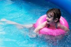 Κορίτσι με το επιπλέον σώμα παιχνιδιών στη λίμνη κατωφλιών Στοκ Φωτογραφίες