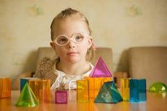 Κορίτσι με το κάτω παιχνίδι συνδρόμου με τις γεωμετρικές μορφές Στοκ Εικόνες